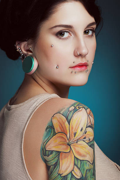 schöne mädchen mit gesichts-piercing und tattoo - ohrringe piercing stock-fotos und bilder