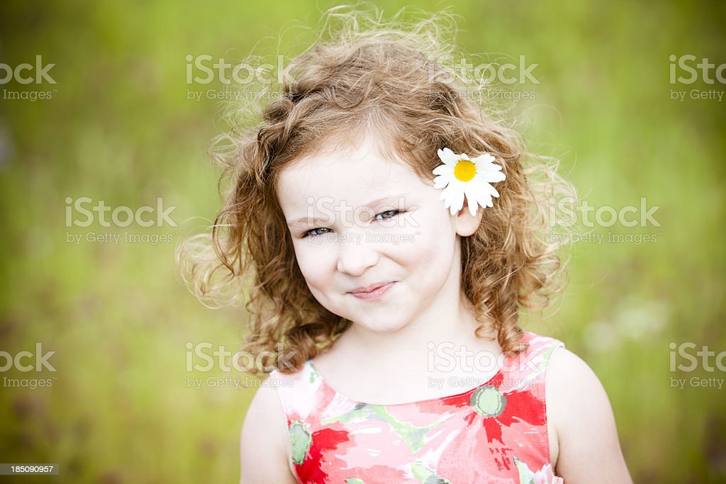 Beautiful girl with flower standing in field. royalty-free stock photo