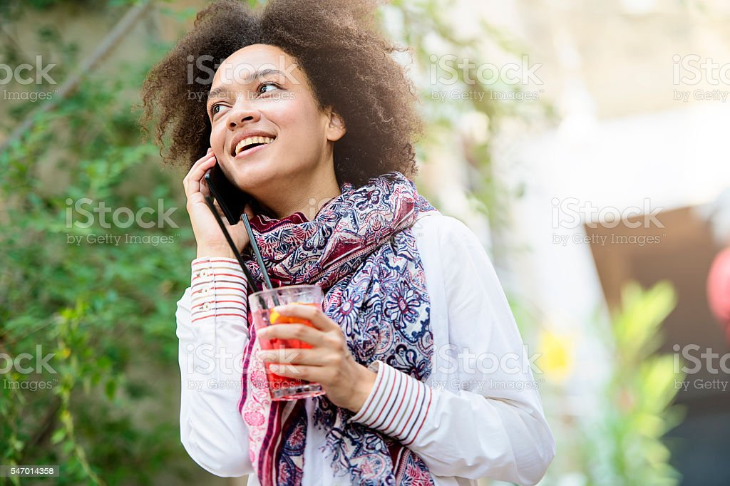 Beautiful girl with fruit cocktail using smartphone stock photo