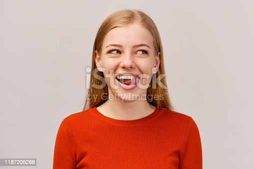 Naughty teenage girl misbehaving sticking out tongue at camera sign of disobedience, protest. Beautiful young girl with ginger long hair wearing red sweater, isolated on white wall in Studio.