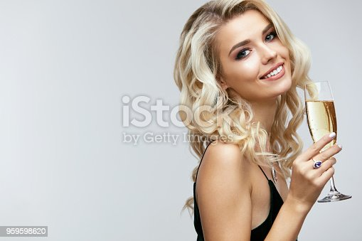 Beautiful Girl With Glass Of Champagne Celebrating. Portrait Of Smiling Young Woman With Long Curly Blonde Hair, Stylish Hairstyle, Beautiful  Glamour Makeup On Beauty Face With Drink. High Quality Image