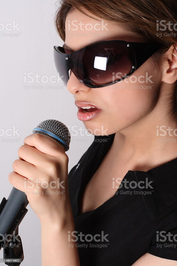 Beautiful girl with glasses and microphone royalty-free stock photo