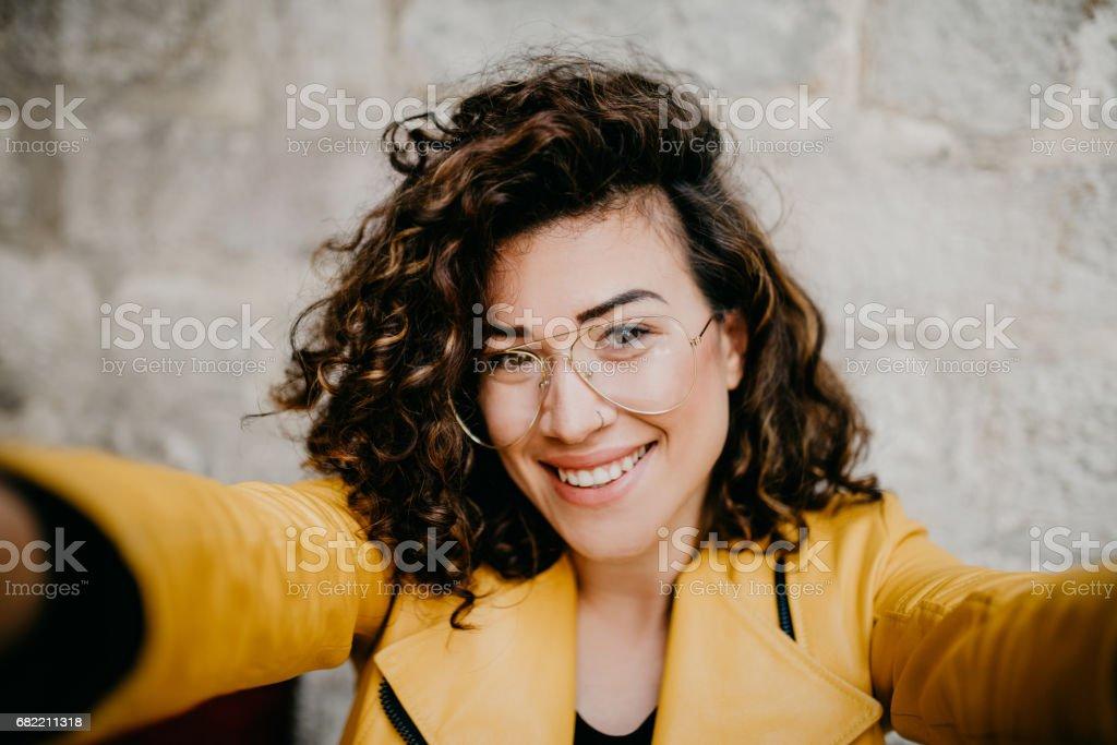 Hermosa chica con gafas y anillo de la nariz tiene un selfie - foto de stock