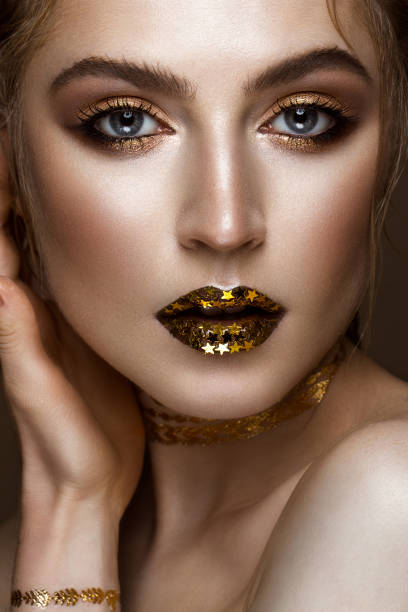 schöne mädchen mit goldenen glänzenden make-up und sterne auf den lippen. beauty gesicht. - promi schmuck stock-fotos und bilder