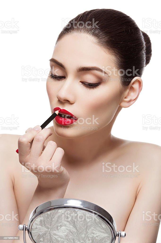 Beautiful girl with lip pencil stock photo