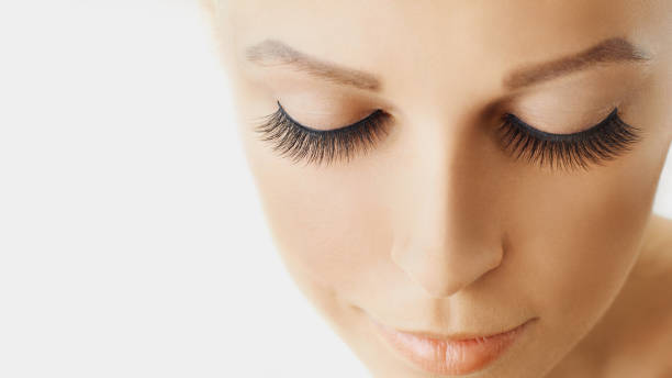 Beautiful girl with long eyelashes and perfect skin Eyelash extensions, cosmetology, beauty and skin care. Close up, macro with copy space false eyelash stock pictures, royalty-free photos & images