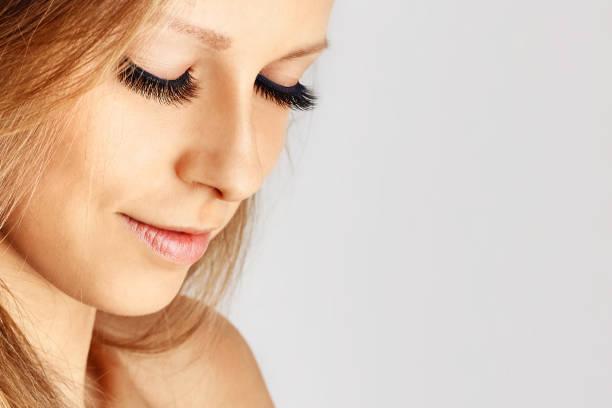 Beautiful girl with long false eyelashes and perfect skin. stock photo