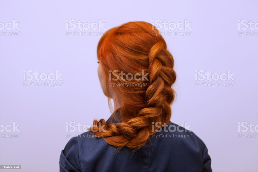 Beautiful girl with long red hair, braided with a French braid, in a beauty salon. stock photo