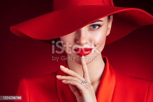 Beautiful girl with make-up wearing red jacket and hat