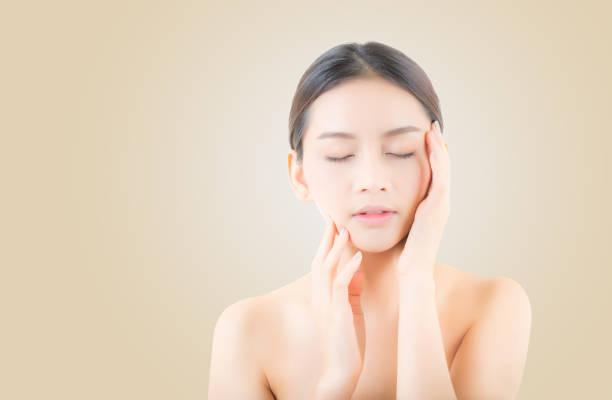 化粧美人の女性肖像画や肌ケア化粧品コンセプト/魅力的な黄色の背景に顔がアジア美少女。 ストックフォト