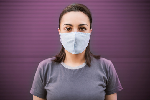 Beautiful girl with medical mask to protect her from virus. Corona virus pandemic