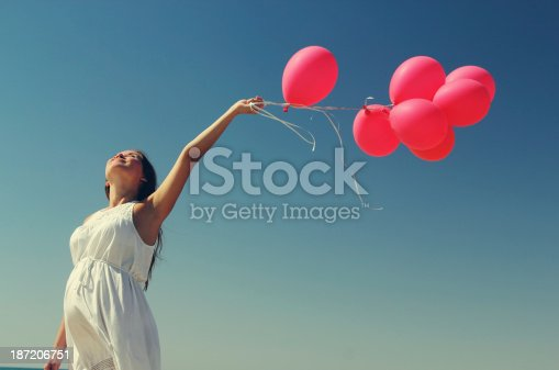 istock Beautiful girl with red balloon at blue sky background 187206751