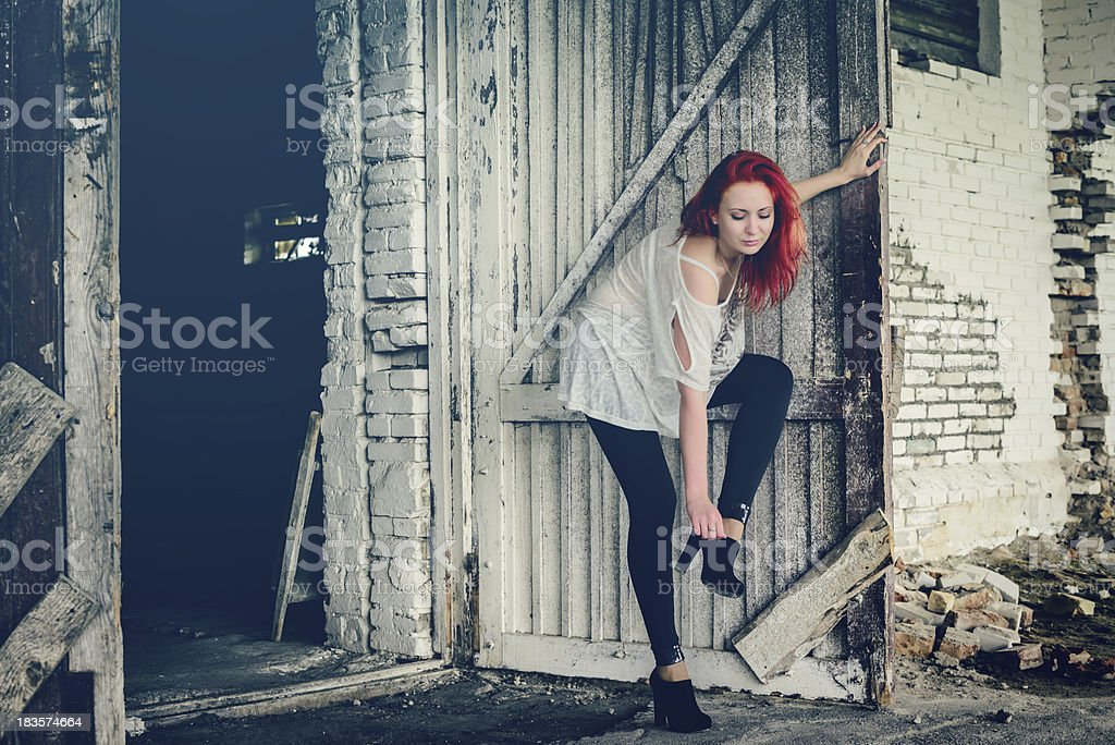 beautiful girl with red hair outdoor against wooden doors royalty-free stock photo