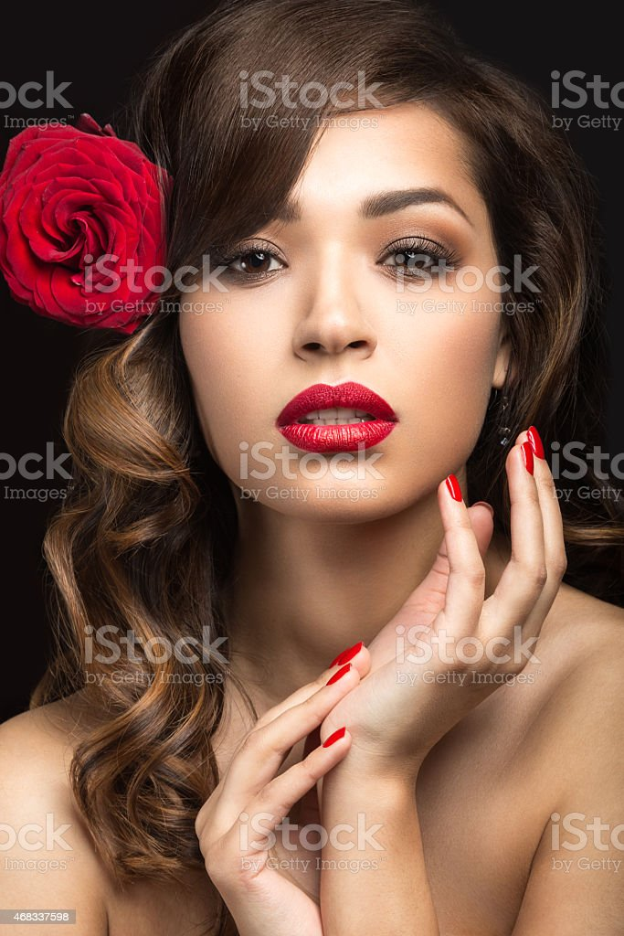 Beautiful girl with red lips and rose in her hair. stock photo