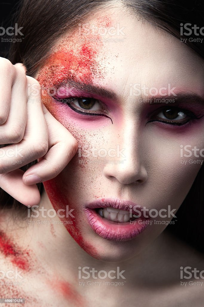beautiful Girl with red paint on her face. stock photo