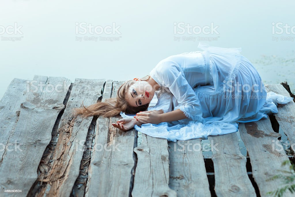 Beautiful girl with sad face lying on a wooden pier. stock photo