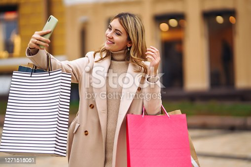 Beautiful girl with shopping bags makes selfie. Young woman holding shopping bags on the city street makes selfie on the phone. Consumerism, purchases, shopping, lifestyle concept.