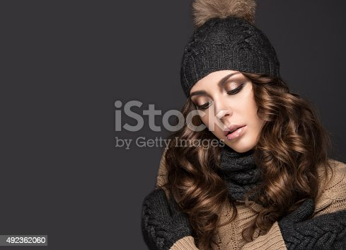 istock Beautiful girl with Smokeymakeup, curls in black knit hat. Warm 492362060