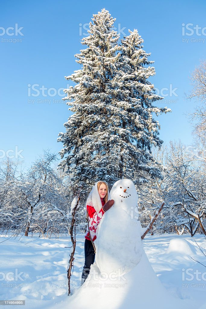 Beautiful girl with snowman near spruce royalty-free stock photo