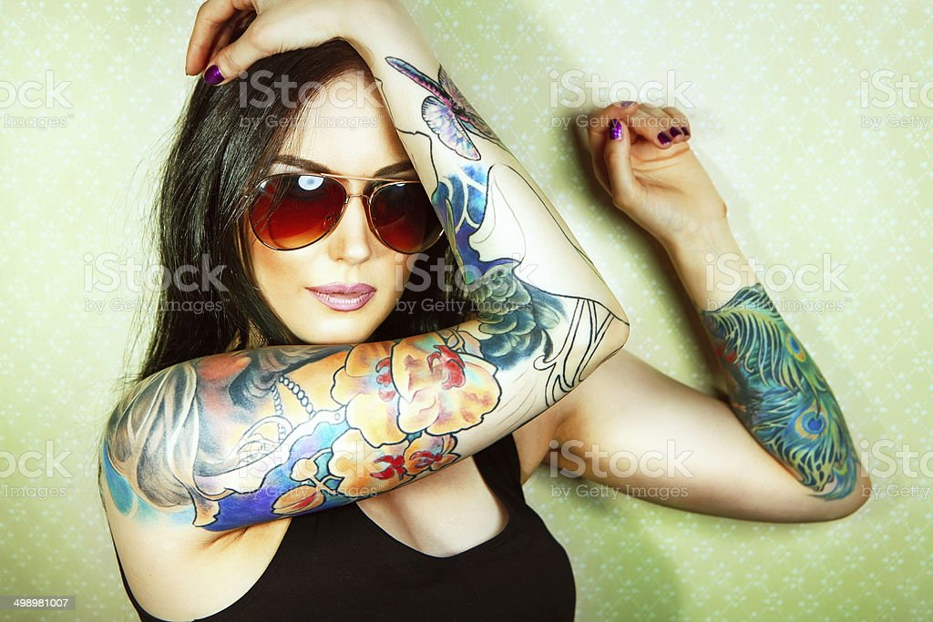 Beautiful girl with stylish make-up and tattooed arms.. stock photo