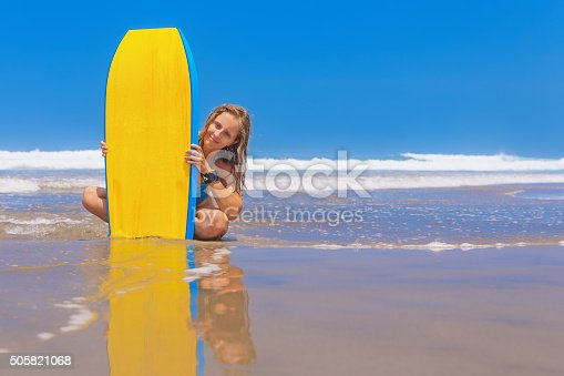 583830686 istock photo Beautiful girl with surf board on sea beach with waves 505821068