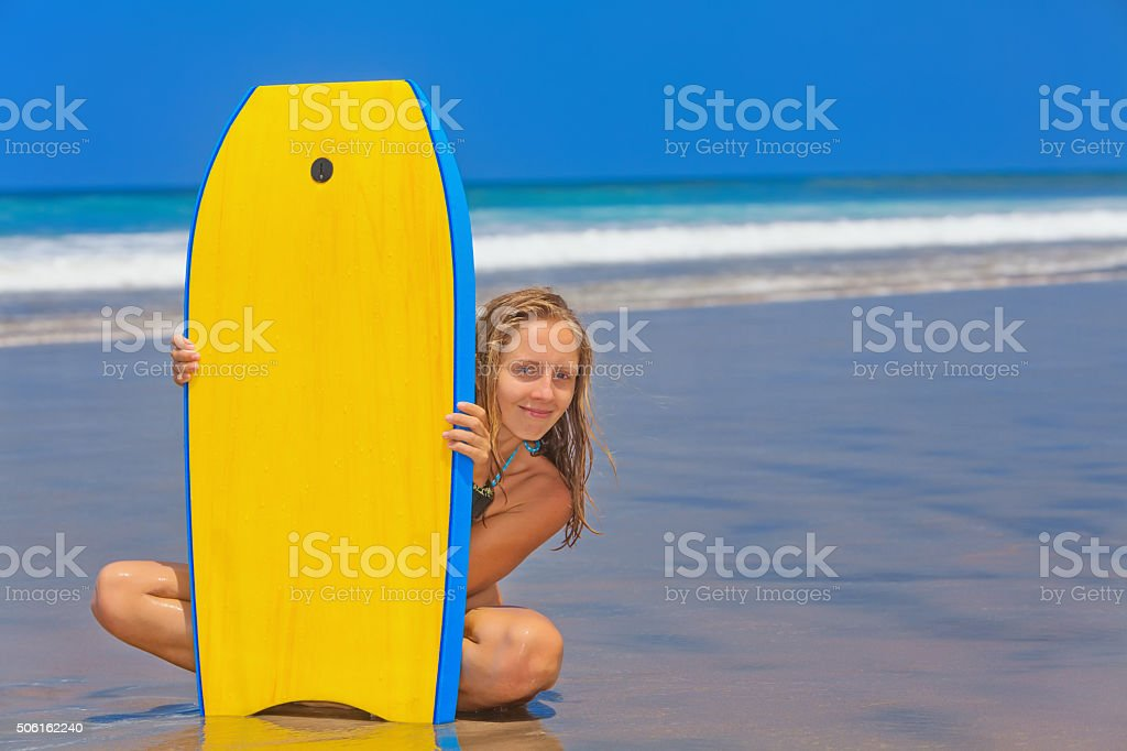 Beautiful girl with surf board on sea beach with waves stock photo