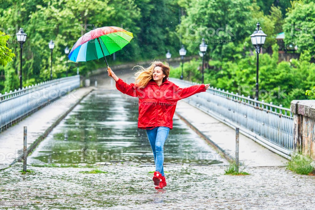 Beautiful girl with umbrella dancing in the rain stock photo
