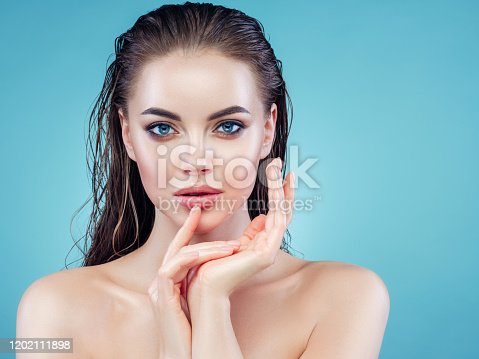 Beautiful girl with wet hair posing against blue background