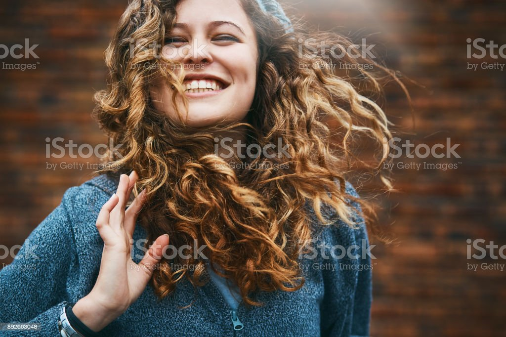 Beautiful girl with winter windblown hair laughs stock photo