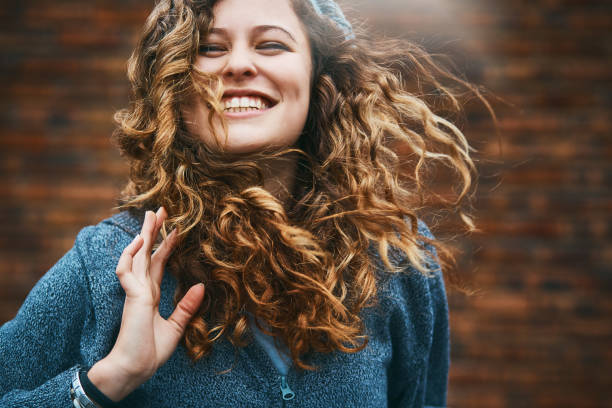 Beautiful girl with winter windblown hair laughs A lovely young woman dressed for winter stands outside, her hair blown by the wind, laughing happily. curly hair stock pictures, royalty-free photos & images