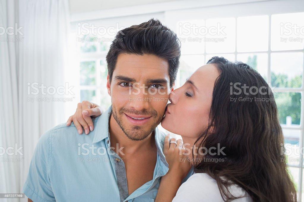 Beautiful girlfriend kissing her boyfriend on the cheek stock photo