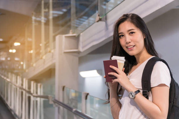 Beautiful Girls Asians : She looks happy Holiday time. For travel to relax. She wearing casual clothes is posing at airport. Have a passport with a cup of coffee in her hand. Copy space. stock photo