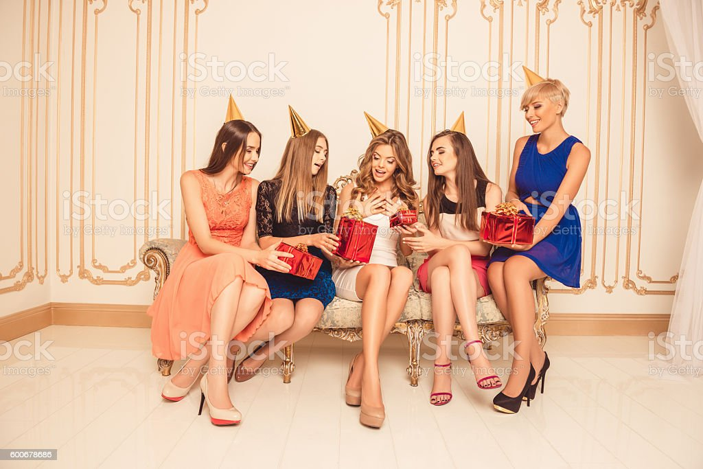 Cтоковое фото Beautiful girls celebrating birthday sitting on the sofa