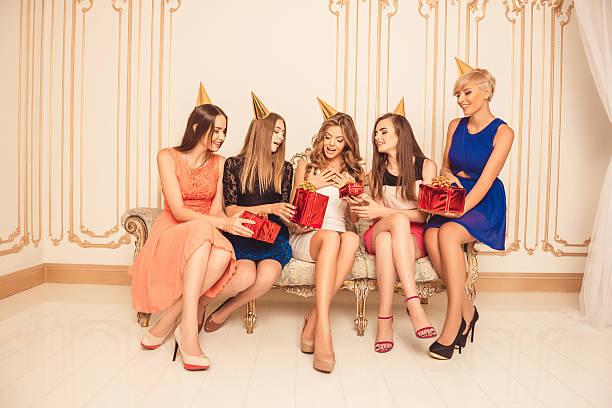 beautiful girls celebrating birthday sitting on the sofa - jugendliche geburtstag geschenke stock-fotos und bilder