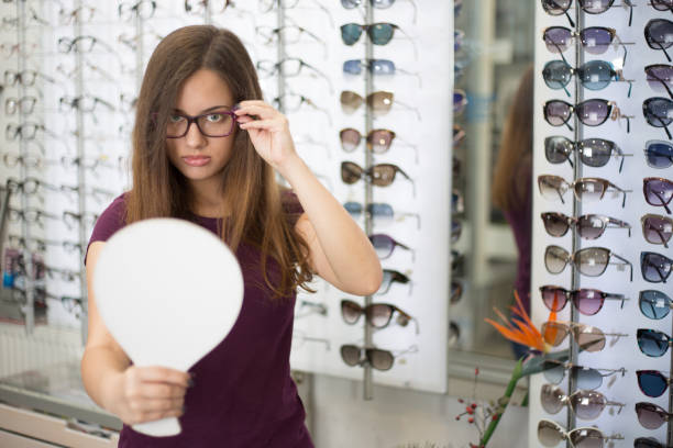 Beautiful girls choosing glasses stock photo