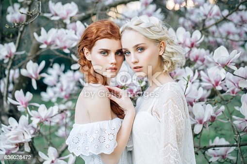istock Beautiful girls on the background of spring bush 636028472