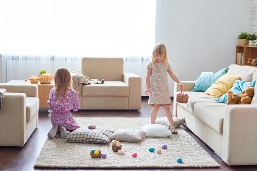 Playful cute girl walking over living room and finding Easter eggs putting them in basket while her sister sitting on carpet
