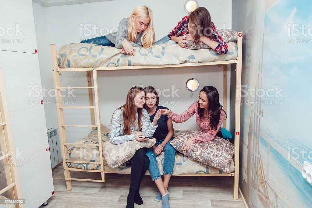 Beautiful girls sitting on a bed in hostel talk and stock photo