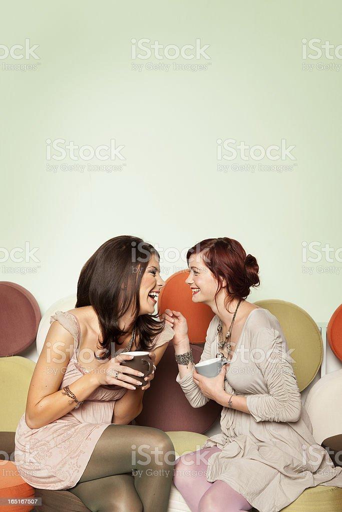 beautiful girls sitting on sofa laughing royalty-free stock photo