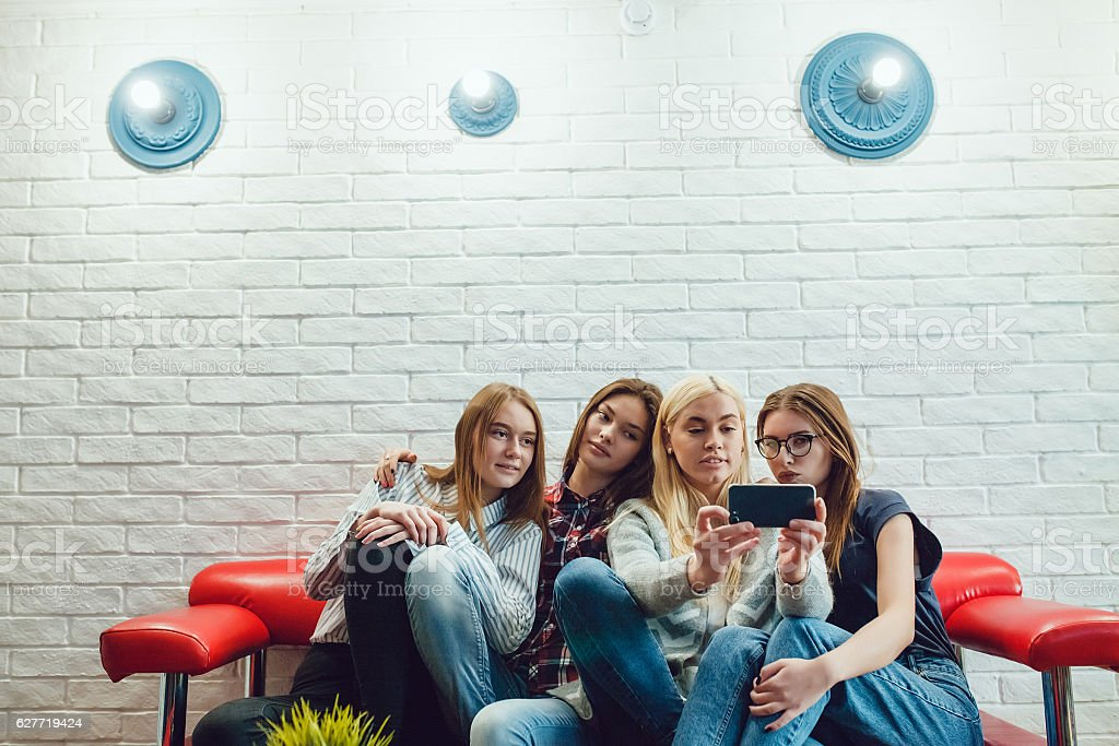 Beautiful girls sitting on the couch, have fun and make stock photo