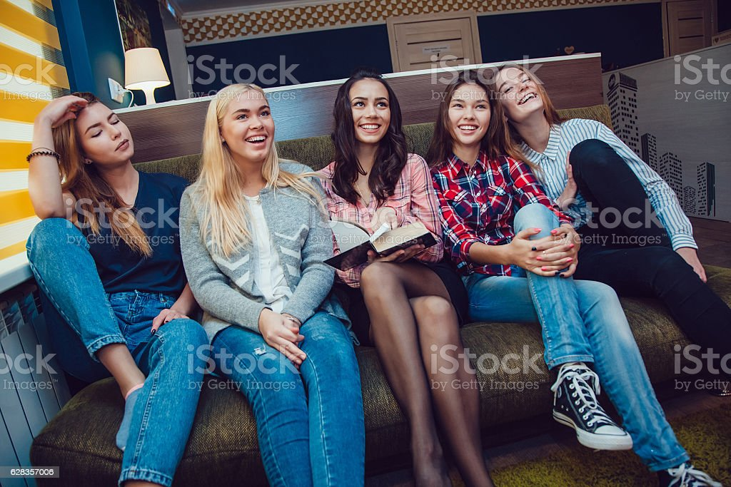 Beautiful girls sitting on the couch, have fun and read stock photo