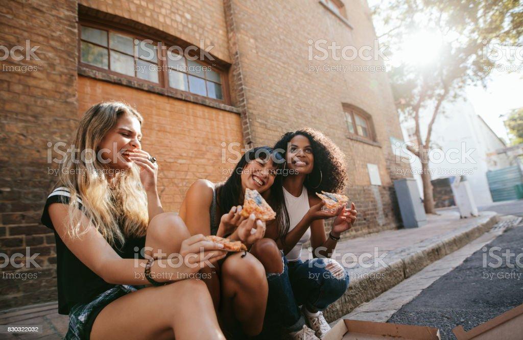 Belas garotas sentado ao ar livre à beira da estrada comendo pizza - foto de acervo