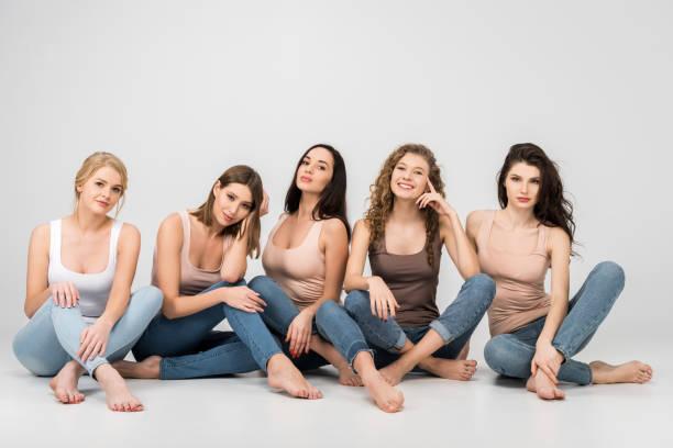 회색 배경에 교차 다리와 함께 앉아있는 동안 웃는 아름 다운 여자 - 5명 뉴스 사진 이미지