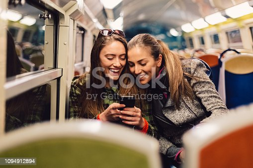 Happy friends traveling at night in public transportation and surfing the net on mobile phone