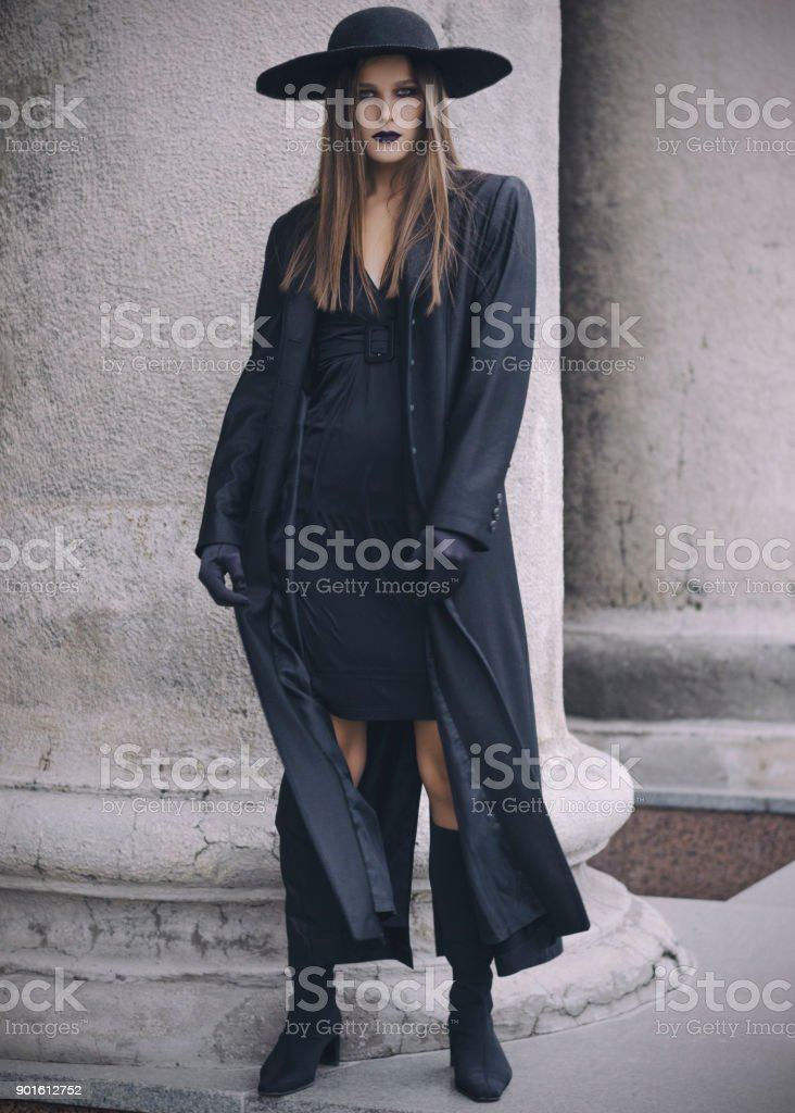 Beautiful gitl in black coat wearing black hat and balck gloves stock photo