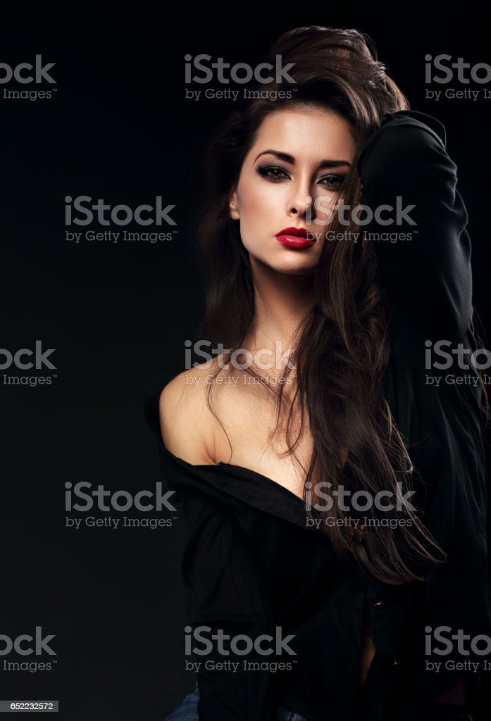 Beautiful glamour female model with long brown hair posing in black shirt on dark background with red lipstick and looking vamp stock photo