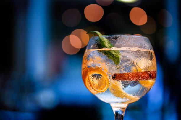 hermoso cristal de ginebra en el mostrador de la barra con fondo borroso en tonos de azul y boke. - cóctel bebida alcohólica fotografías e imágenes de stock