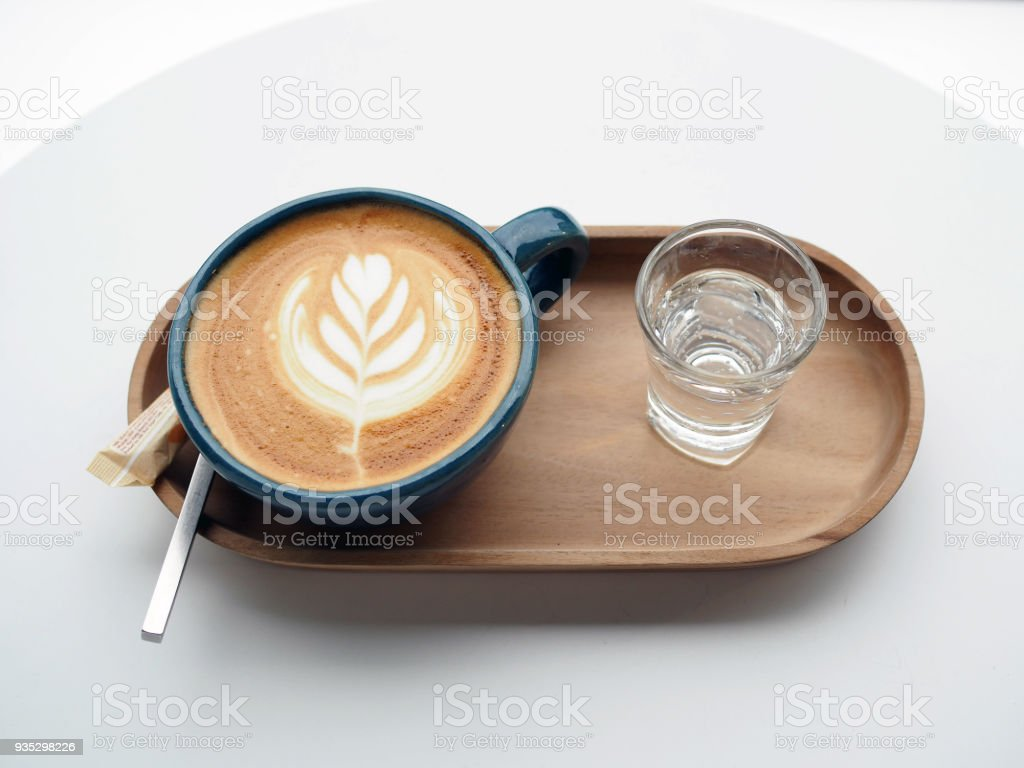 A beautiful glass of hot coffee with Latte Art; flower shape, served with drinking water on wooden tray. stock photo