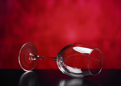 Beautiful glass wine glass on a red background.