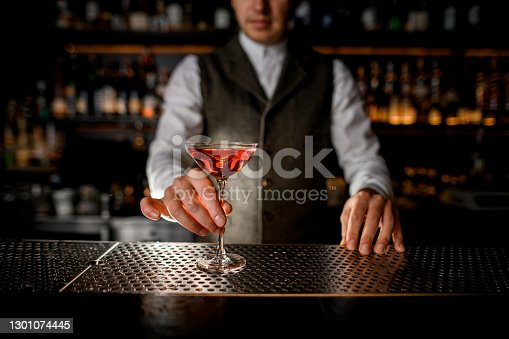 beautiful glass with drink is placed on metal surface of the bar and hand of man bartender holds it